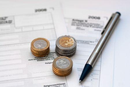 questionaire: Cuestionario alem�n de Impuestos para el a�o 2008 con monedas de euro y un l�piz Foto de archivo