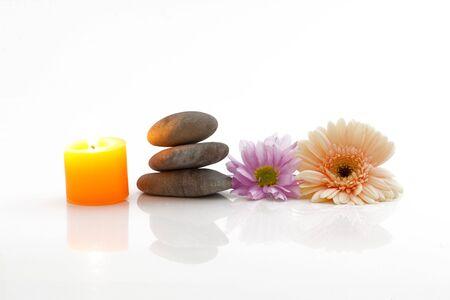 mental object: Un tema a�n la vida de spa con velas, flores y piedras de r�o, aislado en blanco, con reflejos Foto de archivo