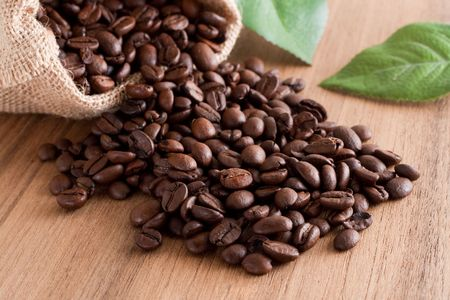 coffee sack: A bunch of coffee beans, falling out of a sack on a wooden background Stock Photo
