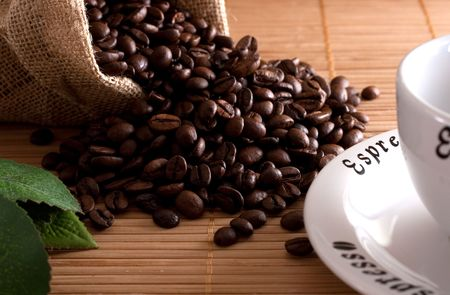 A bunch of coffee beans, falling out of a sack and a cup of fresh coffee on a wooden background Stock Photo - 4913374