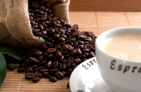 falling out: A bunch of coffee beans, falling out of a sack and a cup of fresh coffee on a wooden background Stock Photo