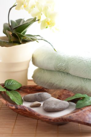 Yellow orchid, massage stones, two towels isolated on white background photo
