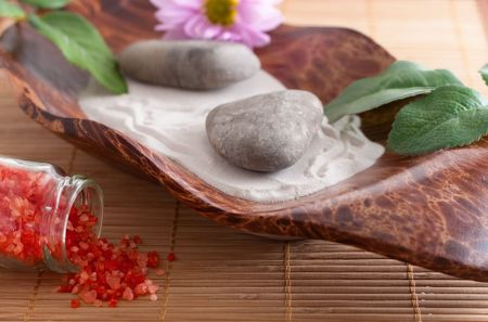Massage stones on sand in a bowl, a purple flower and red bath salt photo