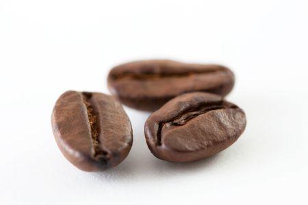 grano de cafe: A cerca disparar de algunos granos de caf� aisladas sobre fondo blanco Foto de archivo