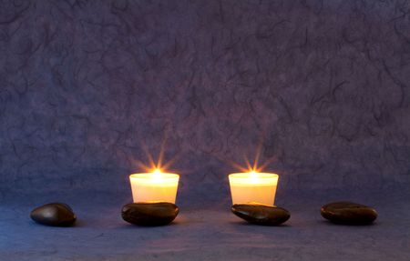 A set of massage stones on bluepurple wallpaper with candles photo