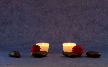 A set of massage stones and roses on bluepurple wallpaper with candles photo
