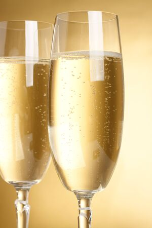 holydays: Two flutes with champagne on golden background Stock Photo