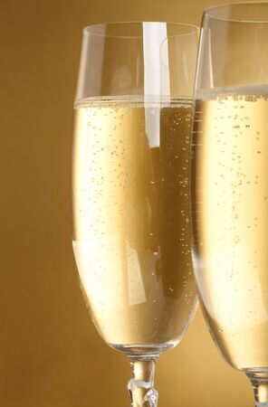 champaign: Two flutes with champagne on golden background Stock Photo