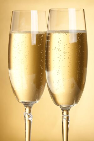 Two flutes with champagne on golden background photo