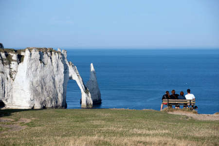 Four people enjoying the views of the Cliffs of Etretat, Normandy, France.