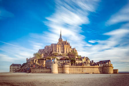 Mont Saint Michel and its abbey with the sea at low tide and clouds moving by the strong wind