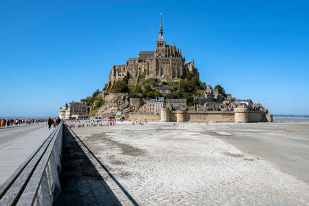 Tourists visiting Mont San Michael and its Abbey at low tide. Редакционное