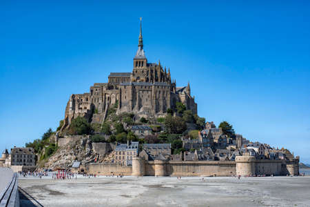 Abbey on Mount Saint Michel at low tide and tourists visiting it.