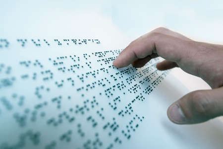 Hand of a blind person reading a text in the language of the blind, Braille