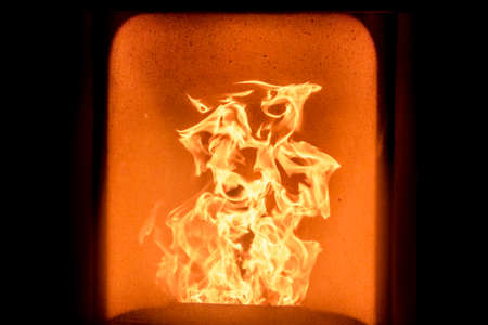 Fire in stove  An orange flame in a warm and black fireplace  photo