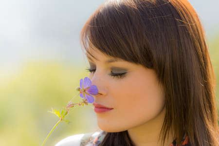 Beautiful meditative girl sniffing a flower  The young woman enjoys the beauty of nature  Wonderful picture with nice colors photo