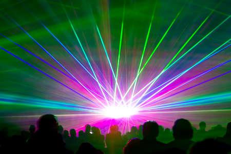 レーザー光線を示します。非常にカラフルなショーの観客のシルエットと偉大なレーザー光線