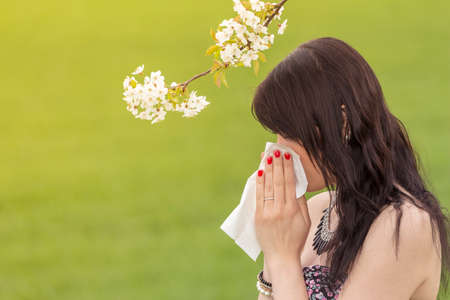 hayfever: Beautiful girl wiping her nose hayfever in spring nature. The beautiful young woman is pained by her allergy every year. She holds a tissue in her hands.