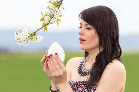 pained: Sneezing hayfever girl is pained in green spring nature. The beautiful young woman is pained by her allergy every year. She holds a tissue in her hands. Stock Photo