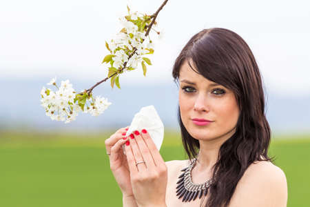 hayfever: Sad hayfever girl in spring nature with blossom branch. The beautiful young woman is pained by her allergy every year. She holds a tissue in her hands. Stock Photo