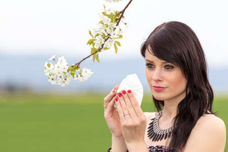 hayfever: Unwell hayfever girl is pained in green spring nature. The beautiful young woman is pained by her allergy every year. She holds a tissue in her hands. Stock Photo