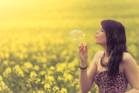 woman blowing: Beautiful woman blowing one soap bubble in yellow summer meadow. The girl has fun in nature and is enjoying her youth.