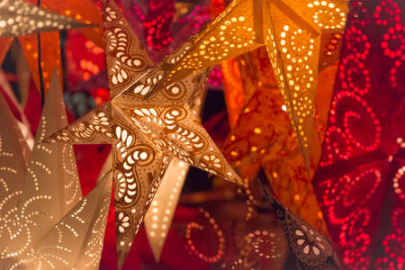 Colorful christmas stars. Shiny red orange golden stars at european christmas market. Part of series.