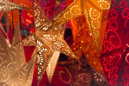 Estrellas coloridas de la Navidad. Estrellas naranja rojo brillante de oro en el mercado de navidad europeo. Parte de la serie. Foto de archivo - 38794702