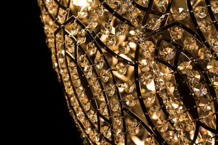 キャンドルを灯して暗い背景と高貴なシャンデリアが。小さな宝石の多くが付いて天井に掛かっている豪華な燭台。