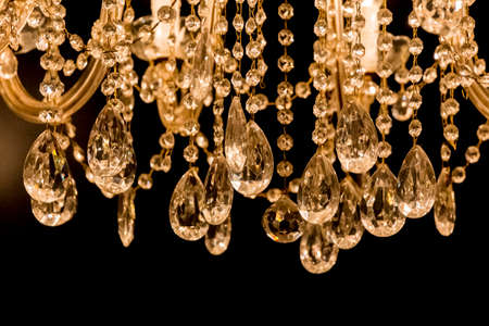 chandeliers: Gallant chandelier with light candles and dark background. Luxury candelabra hanging on ceiling with lots of little gems. Stock Photo