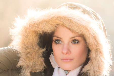 cold season: Beautiful woman with winter coat fur and sunny backlight sun. Wonderful fashion picture with a warm ambient and sunshine in cold season. Foto de archivo