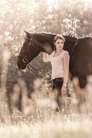 retro lady: Vintage young woman equestrian with horse in summer sun Nature. Scene of a teenager horsewoman holding her best friend animal in a lovely sunny outdoor scene. Vintage portrait format with copy space