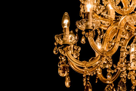 Gallant chandelier with light candles and darkside background. Luxury candelabra hanging on ceiling with lots of little gems. Black Background and copyspace on the leftside
