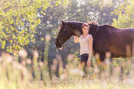landscape format: Beautiful young woman equestrian with horse in summer sun Nature. Portrait of a teenager horsewoman holding her best friend animal in a lovely sunny outdoor scene. Landscape format with copy space