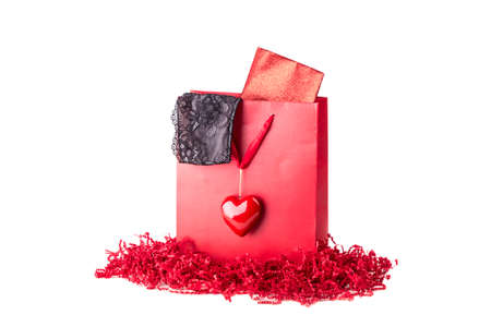 sexy underwear: Beautiful red love present bag with black lingerie and envelope. Sexy lace underwear for girlfriend woman or sweetheart. Nice idea for eg Valentines Day or birthday. Isolated on white background. Stock Photo