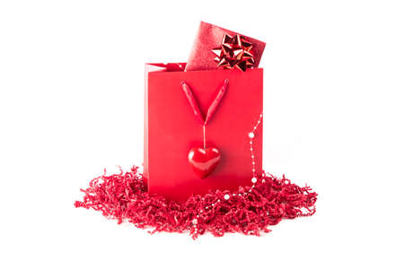 Beautiful surprise present bag with a symbol of love heart. Wonderful red gift with a card inside, maybe voucher or concert tickets for Valentines Day or Mothers Day. Isolated on white background.