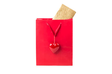 cliche: Beautiful red surprise present bag with heart and golden card. Wonderful gift with envelope inside, maybe a voucher or concert tickets for Valentines Day or Mothers Day. Isolated on white background