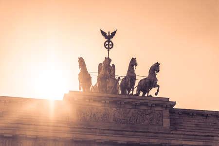 quadriga: Brandenburg gate quadriga sight in berlin city germany europe. Sunset behind the German symbol and landmark Brandenburg Gate at Pariser Platz in the German capital Berlin City.