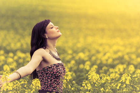 Happy positive woman in sunny summer ocean of yellow flowers. Attractive genuine young girl enjoying the warm summer sun in a wide green and yellow meadow. Copyspace in the right.