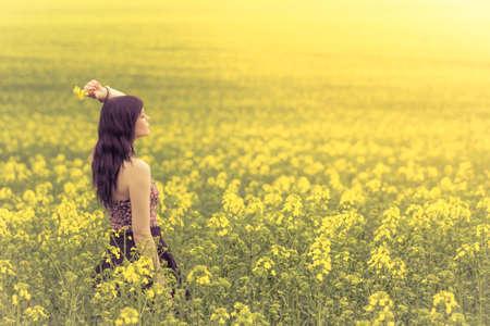 Mooie vrouw in gele bloemen van kant achter op zoek naar rechts. Aantrekkelijke echte jong meisje genieten van de warme zomerzon in een brede groene en gele weide. Deel van de serie.
