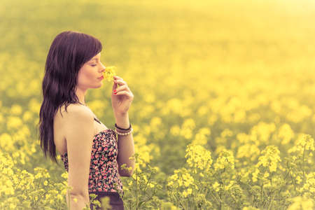 Genuine woman in meadow of yellow flowers sniffing flower. Attractive beautiful young girl enjoying the warm summer sun in a wide green and yellow meadow. Part of series.