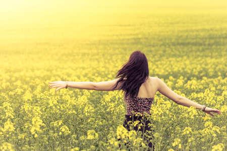 verdadera mujer hermosa en el prado soleado de verano desde detrás del derecho. Atractiva joven auténtica disfrutando del sol de verano caliente en una amplia pradera verde y amarillo. Parte de la serie.