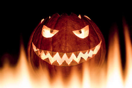 Scary carved halloween pumpkin in hot burning hell fire flames. The big helloween pumpkin has a mad face with glowing eyes and also a glow in its mouth and teeth. Perspective from bottom up. Stock Photo