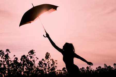 new horizons: Unplugged silhouette woman with red umbrella and wanderlust. Perfect warm scene with girl want to fly. Showing the power of imagination and departure to new horizons like climate change or mindfulness.