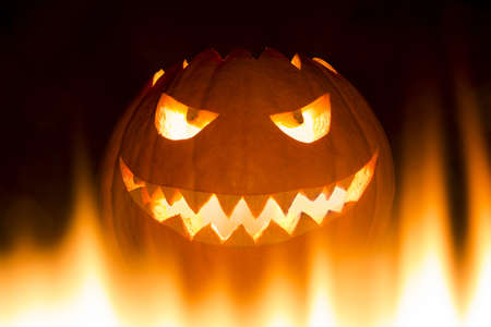Spooky carved halloween pumpkin in hot burning hell fire flames. The big helloween pumpkin has a mad face with glowing eyes and also a glow in its mouth and teeth. Perspective from bottom up. Stock Photo