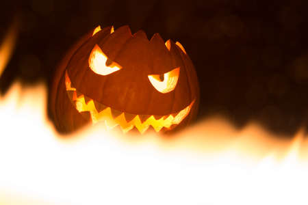Spooky smiling halloween pumpkin in hot burning hell fire flames. The big helloween symbol has a mad face glowing eyes and also a glow in its mouth and teeth. Black orange nightmare of October 31st.
