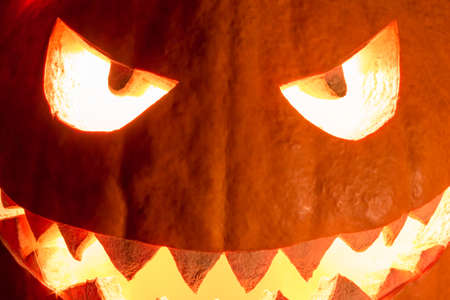 Spooky halloween pumpkin smile with hot burning fire eyes mouth. Big helloween symbol has a glowing closeup mad face and smiling with sharp teeth and bad look. Black orange nightmare of October 31st. Stock Photo