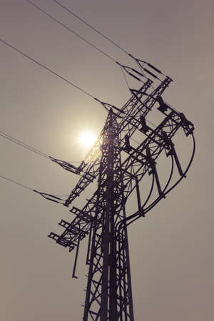 electricity export: High-voltage power line tower carry green electricity sun energy. Ironman business is transmission of renewable sustainable power to prevent climate change and heal the world. Important modernization of grid. Stock Photo