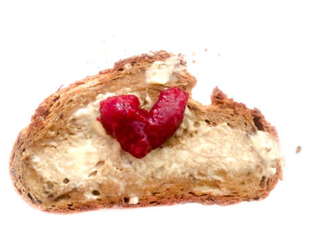 Bread with butter and red heart shape marmelade love symbol. Delicious strawberry or raspberry breakfast surprise present for Mothers Day, girl or boy friend at Valentines Day or anniversary. Isolated on white background.