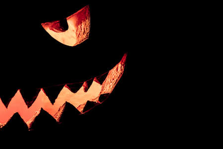 Halloween pumpkin half face smile hot burning fire eyes mouth. Big spooky helloween symbol has a glowing mad face and smiling with sharp teeth and bad look. Black orange nightmare of October 31st.